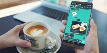 cara menyimpan status wa orang lain membuat watermark - female hand holding smart phone and drinking coffee in a modern cafe laptop computer on desk t20 G07o11 360x180 - 7 Aplikasi Membuat Watermark di Foto Terbaik 2021