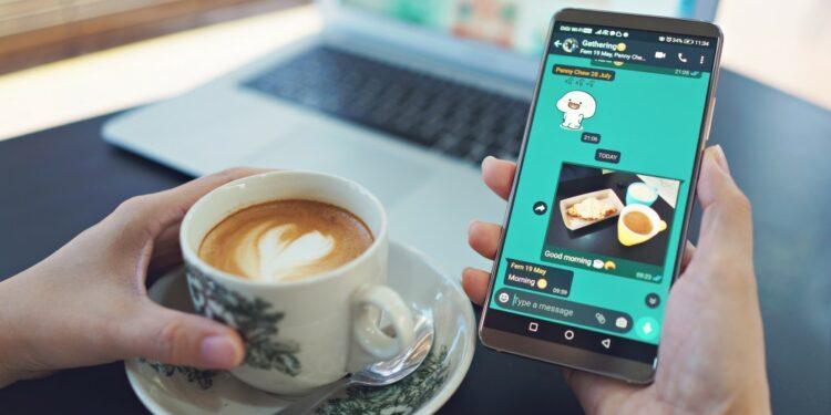 cara menyimpan status wa orang lain cara menyimpan status wa orang lain - female hand holding smart phone and drinking coffee in a modern cafe laptop computer on desk t20 G07o11 750x375 - Cara Menyimpan Status WA Orang Lain