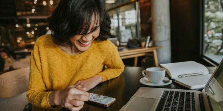 paket internet unlimited paket internet unlimited pandemi - young hipster woman smiling sitting in coffee shop using smartphone smiling technology happy internet t20 XznLE6 750x375 - Cara Memilih Paket Internet Unlimited Kala Pandemi