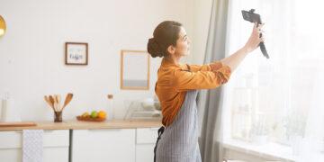 Side view portrait of beautiful young woman holding smartphone while filming story video for social media channel, copy space keuntungan menggunakan ovo - HP dengan Fitur Video 4K yang cocok untuk vlog 360x180 - Keuntungan Menggunakan OVO
