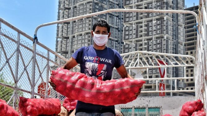 ekspor arab saudi memasarkan produk ukm di arab saudi - man wearing a protective face mask unloading a very heavy sack of red onions from his truck they are t20 4ejE9R 668x375 - Kiat Memasarkan Produk UKM di Arab Saudi